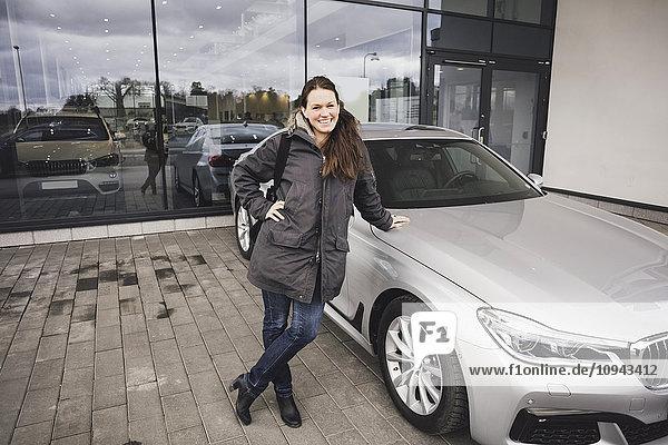 Porträt einer lächelnden Frau  die am Auto gegen den Ausstellungsraum steht.
