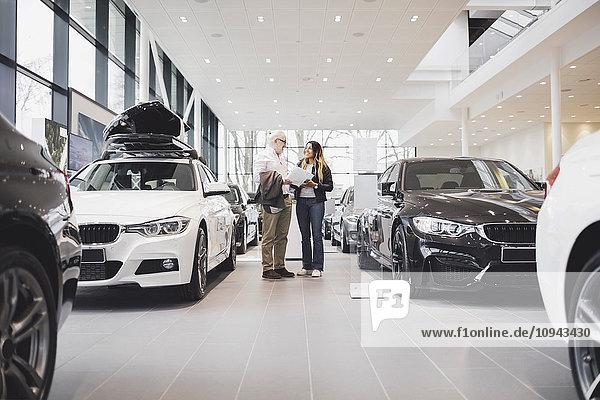 Mann und Frau mit Papier inmitten von Autos im Showroom