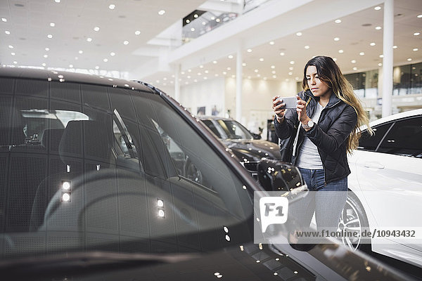 Junge Frau fotografiert neues Auto mit dem Handy im Showroom
