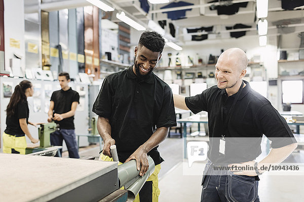 Lächelnder Lehrer mit Schüler bei der Blechbearbeitung in der Werkstatt