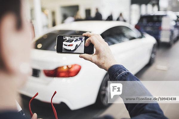 Seniorin fotografiert neues Auto per Handy im Showroom