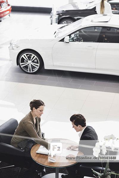 Verkäufer erklärt dem Kunden das Dokument im Autohaus