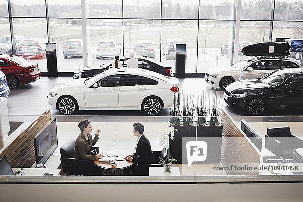 Hoher Blickwinkel auf die Verkäuferin und den Kunden bei der Besprechung im Showroom