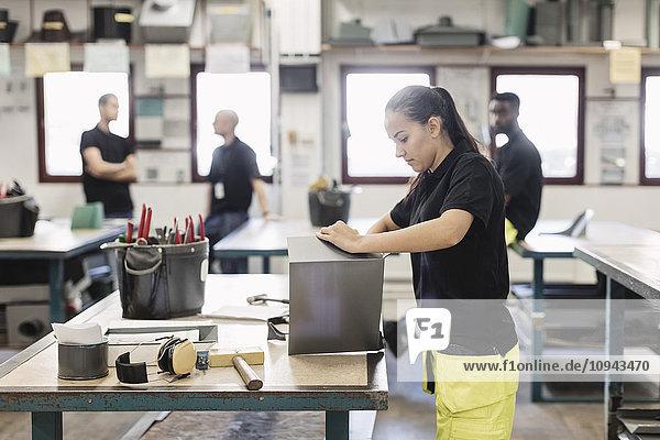 Seitenansicht der Studentin bei der Blechbearbeitung mit Mitarbeitern im Hintergrund