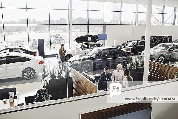 Autoverkäufer im Gespräch mit Kunden am Schreibtisch im Showroom