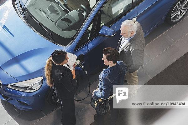 Großer Blickwinkel auf die Verkäuferin im Kundengespräch im Autohaus