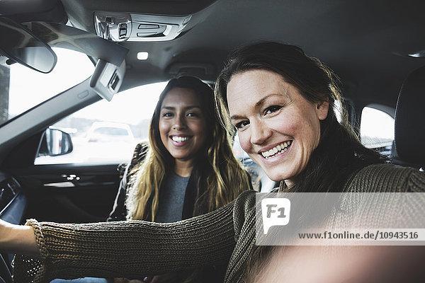 Porträt von lächelnden Freunden im Auto im Showroom