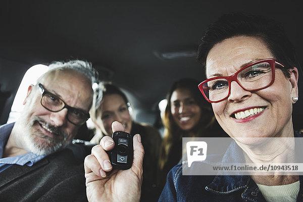 Lächelnde Seniorenfrau mit Fernbedienung im Auto sitzend