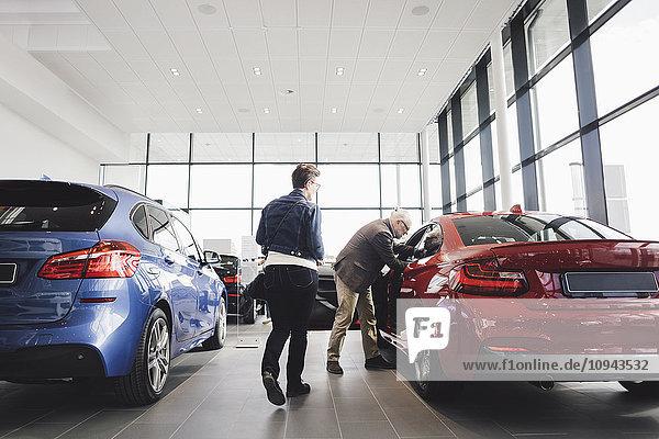 Senior Mann und Frau untersuchen Auto im Showroom