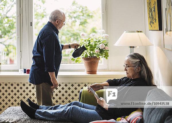 Volle Länge der älteren Frau mit digitaler Tablette  während der Mann zu Hause Blumen gießt.