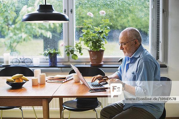 Seitenansicht des älteren Mannes mit Kreditkarte für den Online-Shopping zu Hause