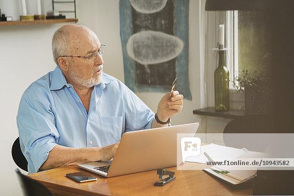 Senior Mann mit Kreditkarte für die Bezahlung der Rechnung am Tisch