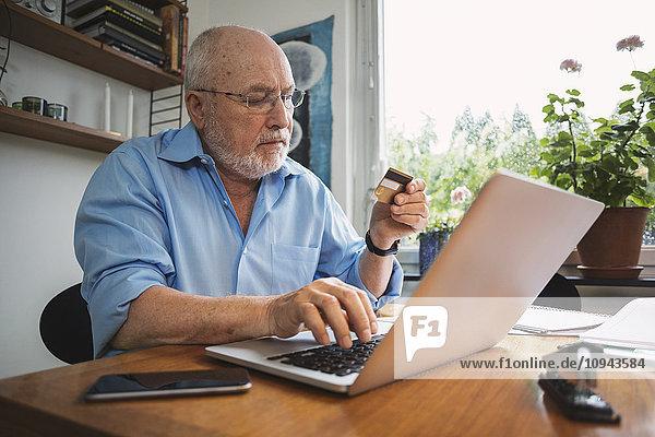 Senior Mann mit Kreditkarte für die Bezahlung der Rechnung zu Hause