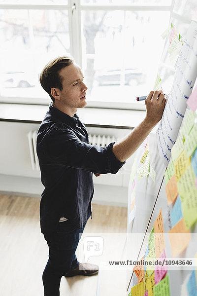Geschäftsmann schreibt auf Whiteboard im Kreativbüro