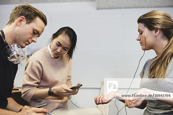 Ingenieure überprüfen Workout-App auf Frau im Büro