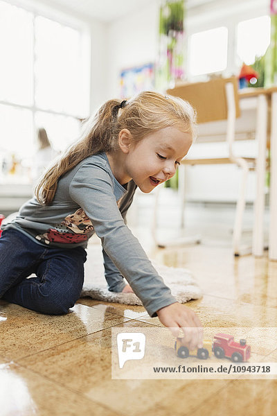 Glückliches Mädchen spielt mit Spielzeugauto auf dem Boden im Klassenzimmer