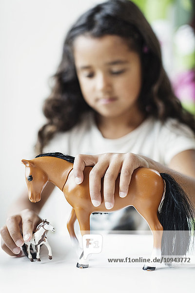 Mädchen spielt mit Spielzeugpferd bei Tisch