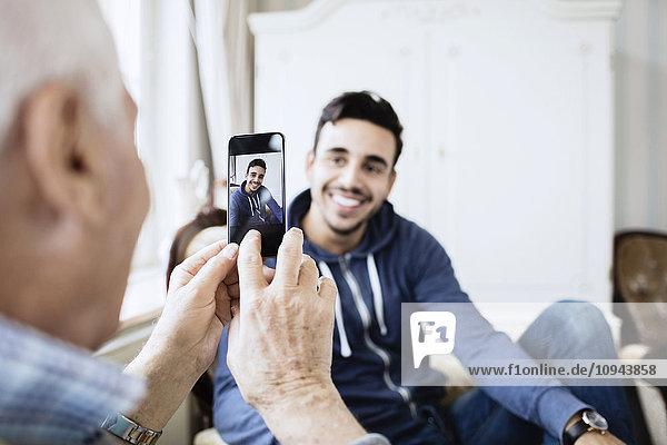 Senior Mann fotografiert Hausmeister durch Smartphone