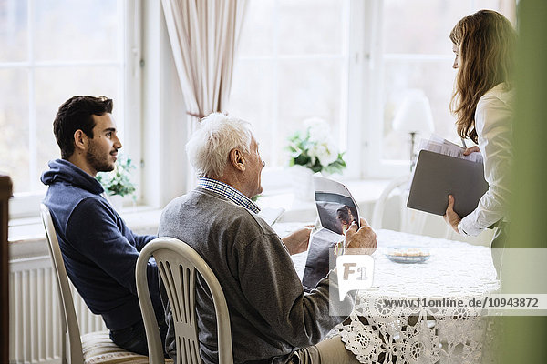 Älterer Mann mit Betreuern im Pflegeheim