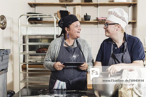Lächelnde Bäckerin sieht beim Backen in der Küche Kollegin an
