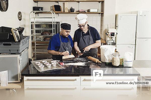 Junger Mann zeigt dem Mitarbeiter beim Kochen in der Küche ein digitales Tablett.