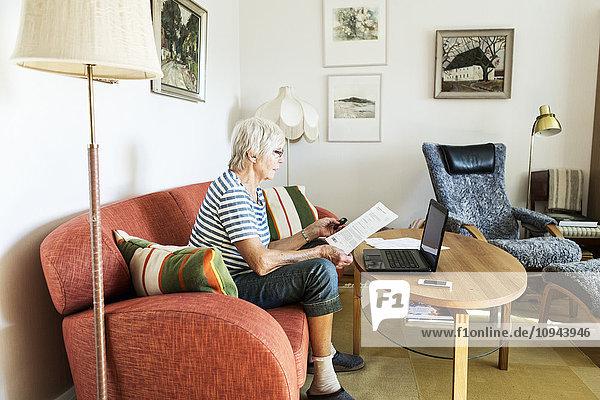 Seniorenfrau analysiert Dokument während der Nutzung des Laptops zu Hause