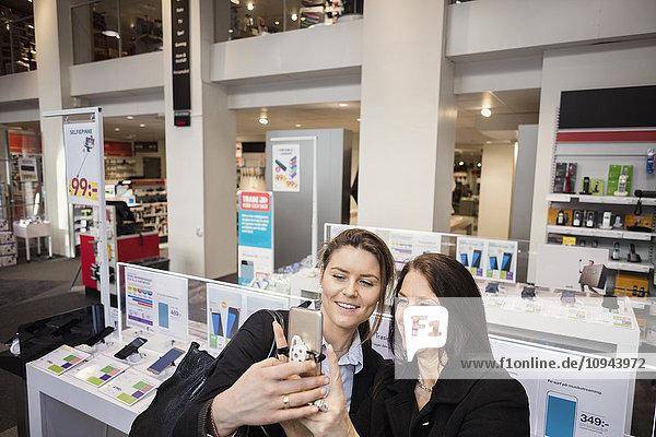Hochwinkelansicht von glücklichen weiblichen Kunden  die Selfie im Geschäft haben.