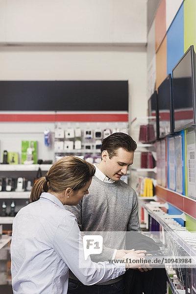 Verkäuferin unterstützt den männlichen Kunden beim Kauf der Telefonabdeckung im Geschäft