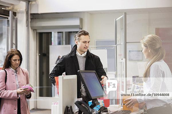 Männlicher Kunde im Gespräch mit einer Frau  die an der Kasse im Ausstellungsraum steht.