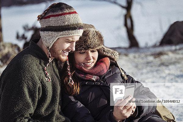 Lächelndes Paar mit Smartphone beim Entspannen auf schneebedecktem Feld