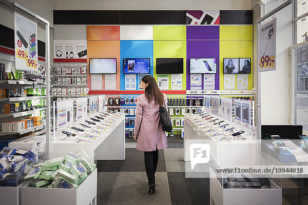 Rear view of female customer viewing smart phones in store