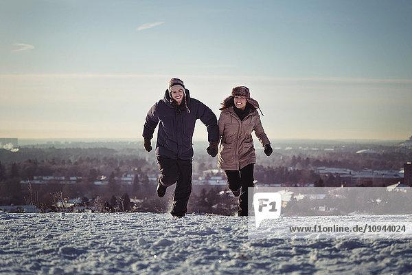 Volle Länge des glücklichen Paares auf schneebedeckten Bergen