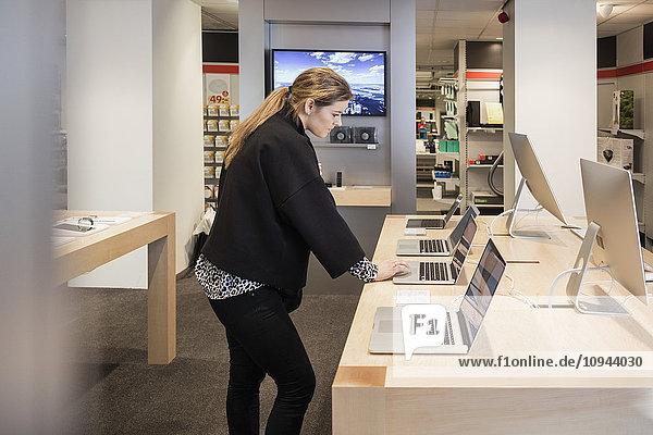 Seitenansicht der Frau mit Laptop beim Stehen am Tisch im Geschäft