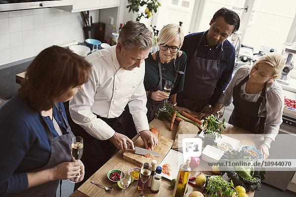 Konzentrierte Studenten beim Lachsschneiden in der Küche