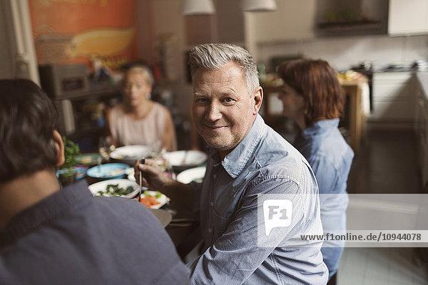 Porträt eines glücklichen reifen Mannes  der mit Freunden am Tisch sitzt