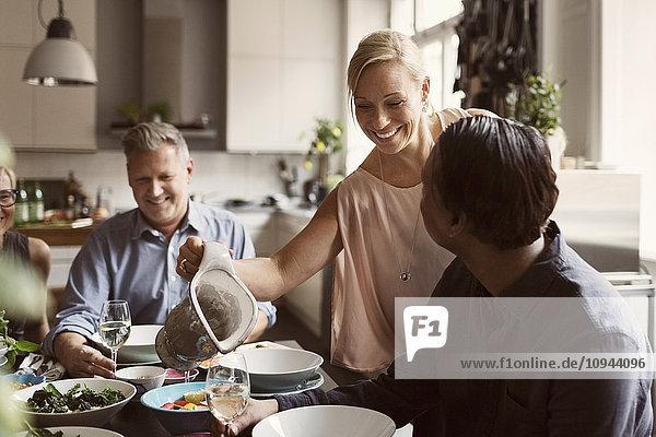Glückliche Frau  die dem reifen Mann am Tisch einen Drink serviert.