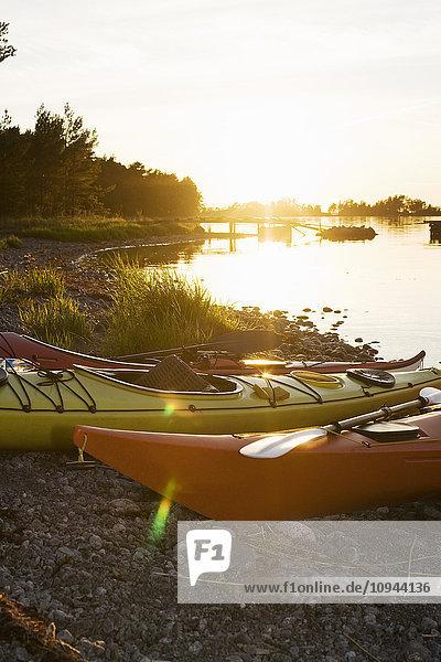 Kajaks am Seeufer bei Sonnenuntergang vertäut