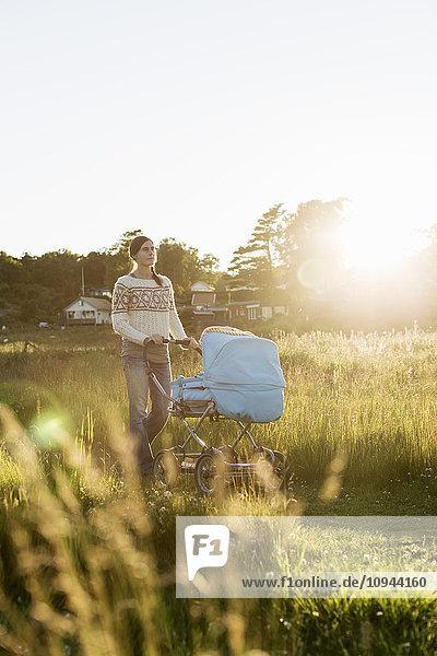 Nachdenkliche Frau  die bei Sonnenuntergang mit dem Kinderwagen auf dem Feld läuft.