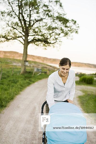 Frau lächelt und schaut Kinderwagen auf der Straße an