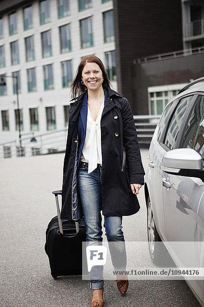 Volle Länge der Frau beim Gehen mit Gepäck