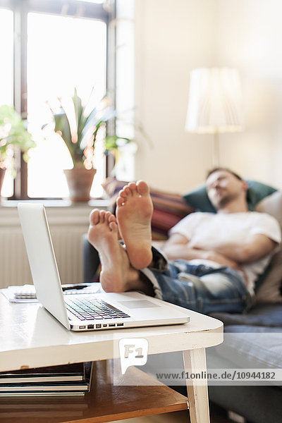 Man lying on sofa by laptop at table
