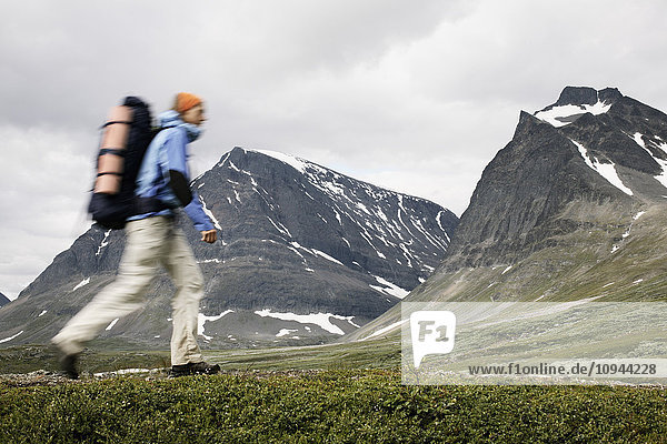 Blurred motion of person walking against mountains
