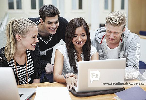 Junge glückliche Freunde mit dem Laptop