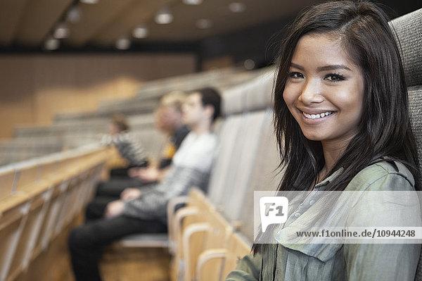 Porträt einer glücklichen jungen Frau im Auditorium mit Freunden im Hintergrund