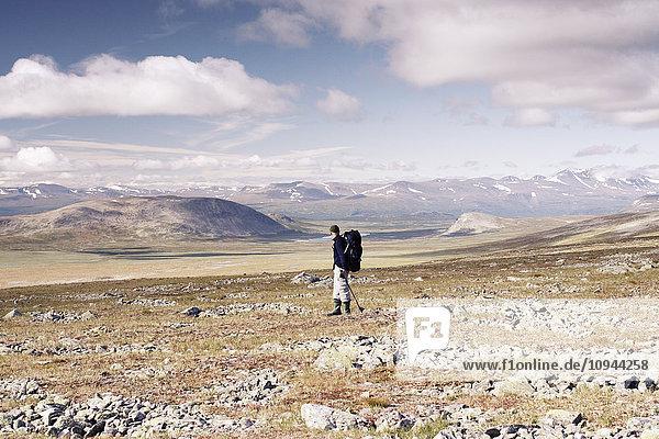 Mann steht auf Landschaft gegen Himmel