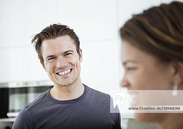Porträt eines lächelnden erwachsenen Mannes mit Frau im Vordergrund