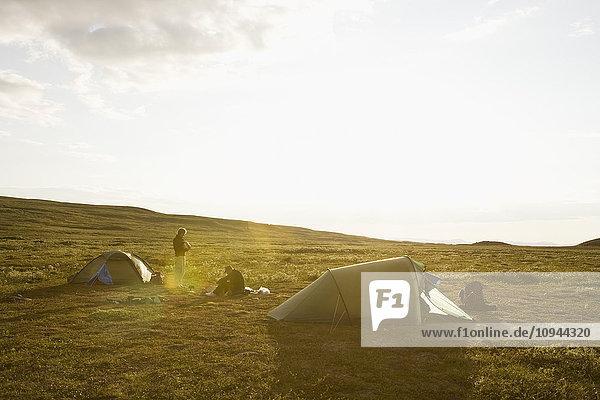 Männer beim Zelten in der Landschaft gegen den Himmel bei Sonnenschein