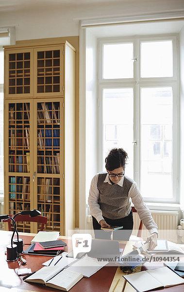 Rechtsanwältin hält Buch  während sie in der Bibliothek am Tisch steht.