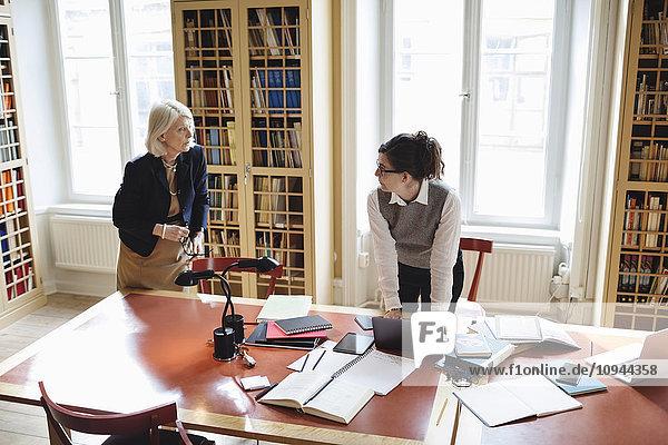 Senioranwältin im Gespräch mit Mitarbeiterin bei Tisch in der Bibliothek