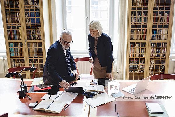 Senior Anwälte mit Laptop am Tisch in der Bibliothek